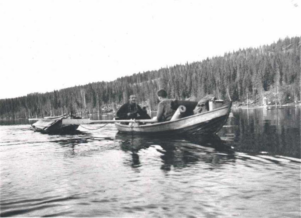 To personer i en robåt ute på et vann. En båt på slepp. Skog i bakgrunnen.