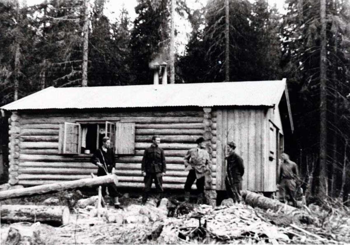 Fem personer utenfor en tømmerhytte i skogen. Menn.
