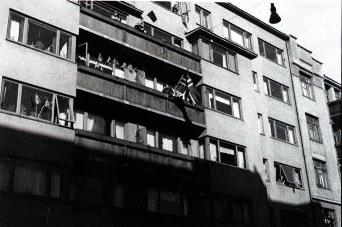 Bygård med flere personer på ballkongene og i vinduene. Norske flagg i vinduene og på ballkongene.