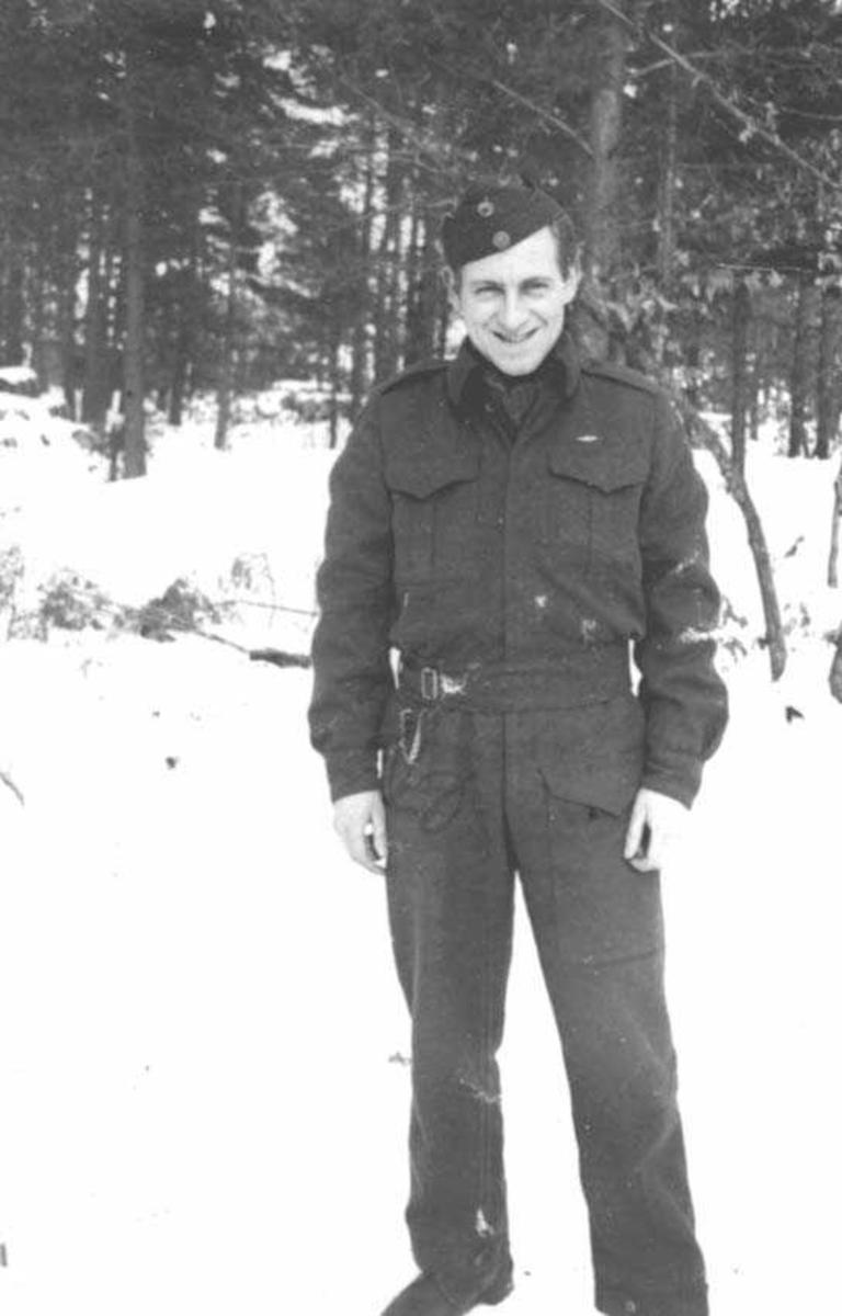En person. Mann i militæruniform. Trær i bakgrunnen.