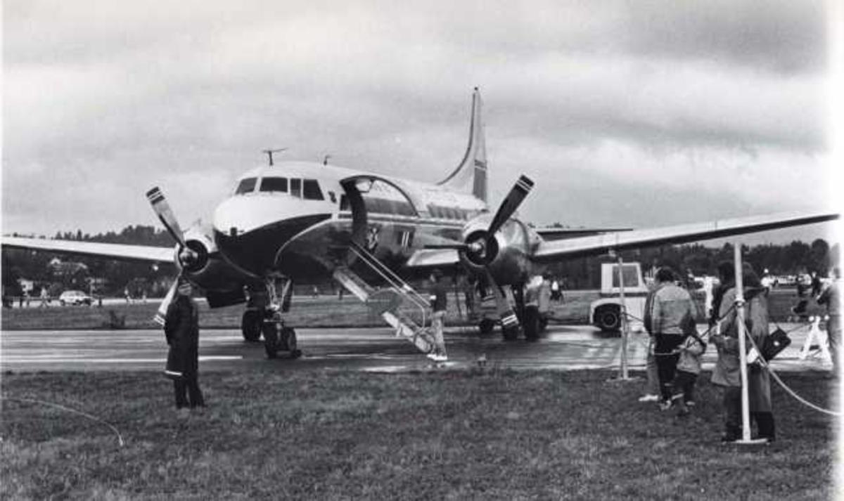 Lufthavn. Et fly på bakken, Convair CV440-75 Metropolitan. Noen personer ved flyet.