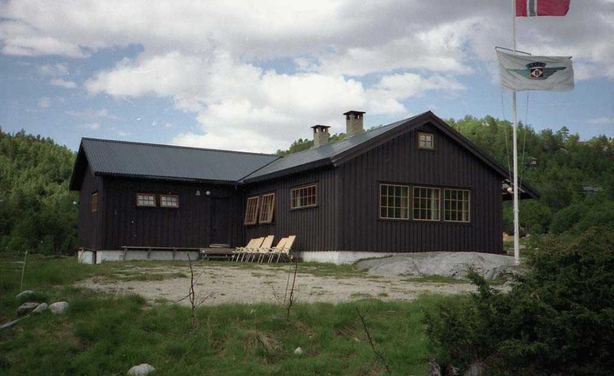 Hytte med skog i bakgrunn. Solstoler langs vegg. Flaggstang med norsk flagg og Braathens SAFE flagg.