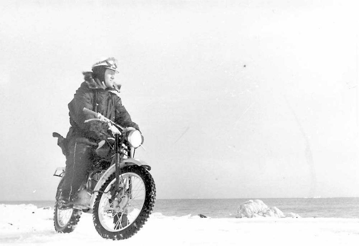 En person som sitter på en motorsykkel. Snø på bakken.
