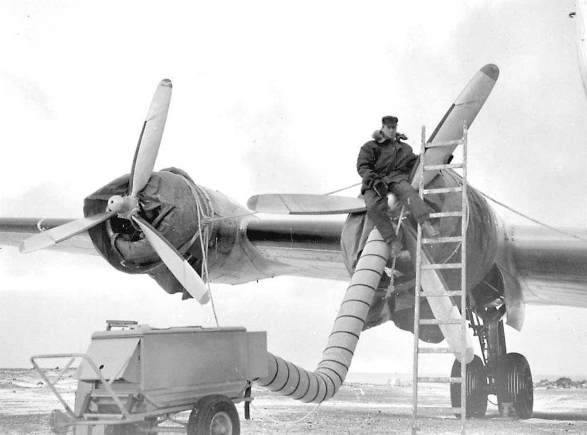 En person som sitter på propellen til en Douglas DC-4 Skymaster. Oppvarmingsmaskin er tilkoblet ene motoren. Begge motorinntakene er tildekket.