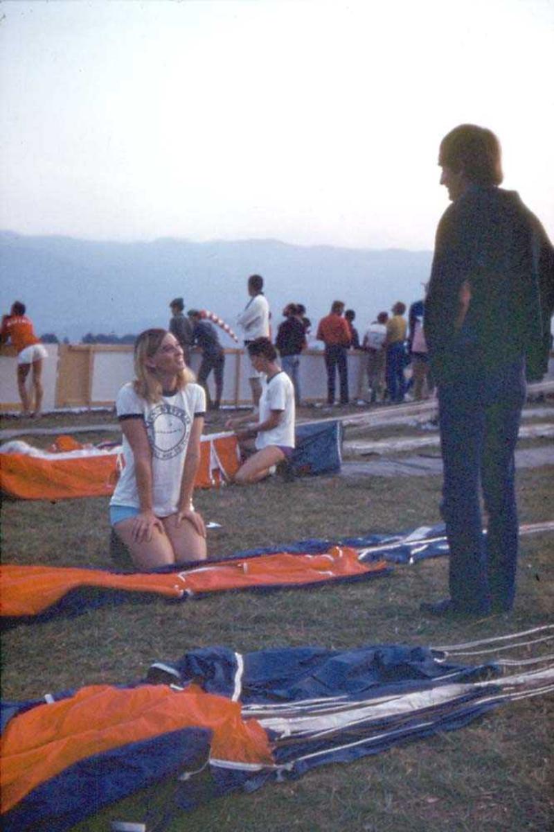 To personer som sitter og pakker fallskjermer. Flere personer i bakgrunnen.