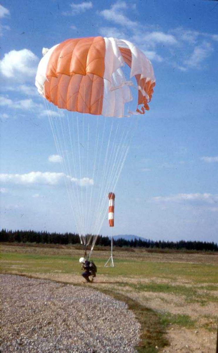 En fallskjermhopper som lander, har føttene på bakken. Vindpølse i bakgrunnen.