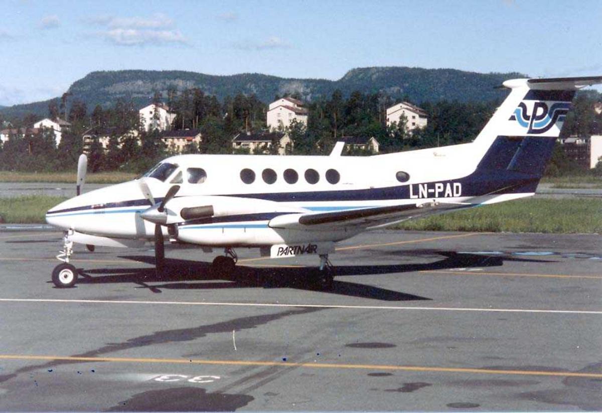 Lufthavn. Ett fly på bakken, Beechraft Super King Air 200 LN-PAD fra Partnair. Bygninger og fjell i bakgrunnen.