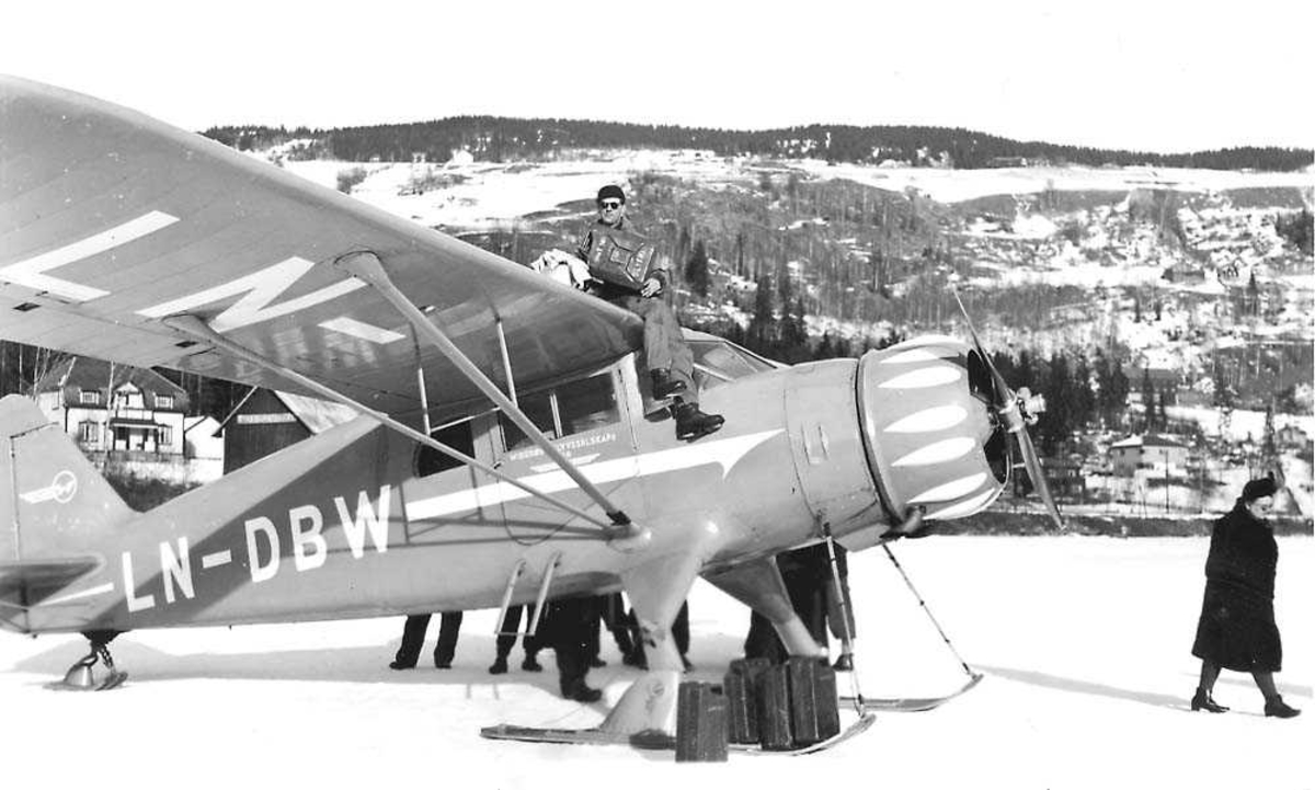 Ett fly på bakken, C-5 Polar  med skiunderstell LN-DBW fra Widerøes Flyveselskap A/S. Flere bensinkanner ved flyet. En person sitter på vingen og fyller bensin på flyet fra en bensinkanne. Flere personer rundt flyet. Snø på bakken.