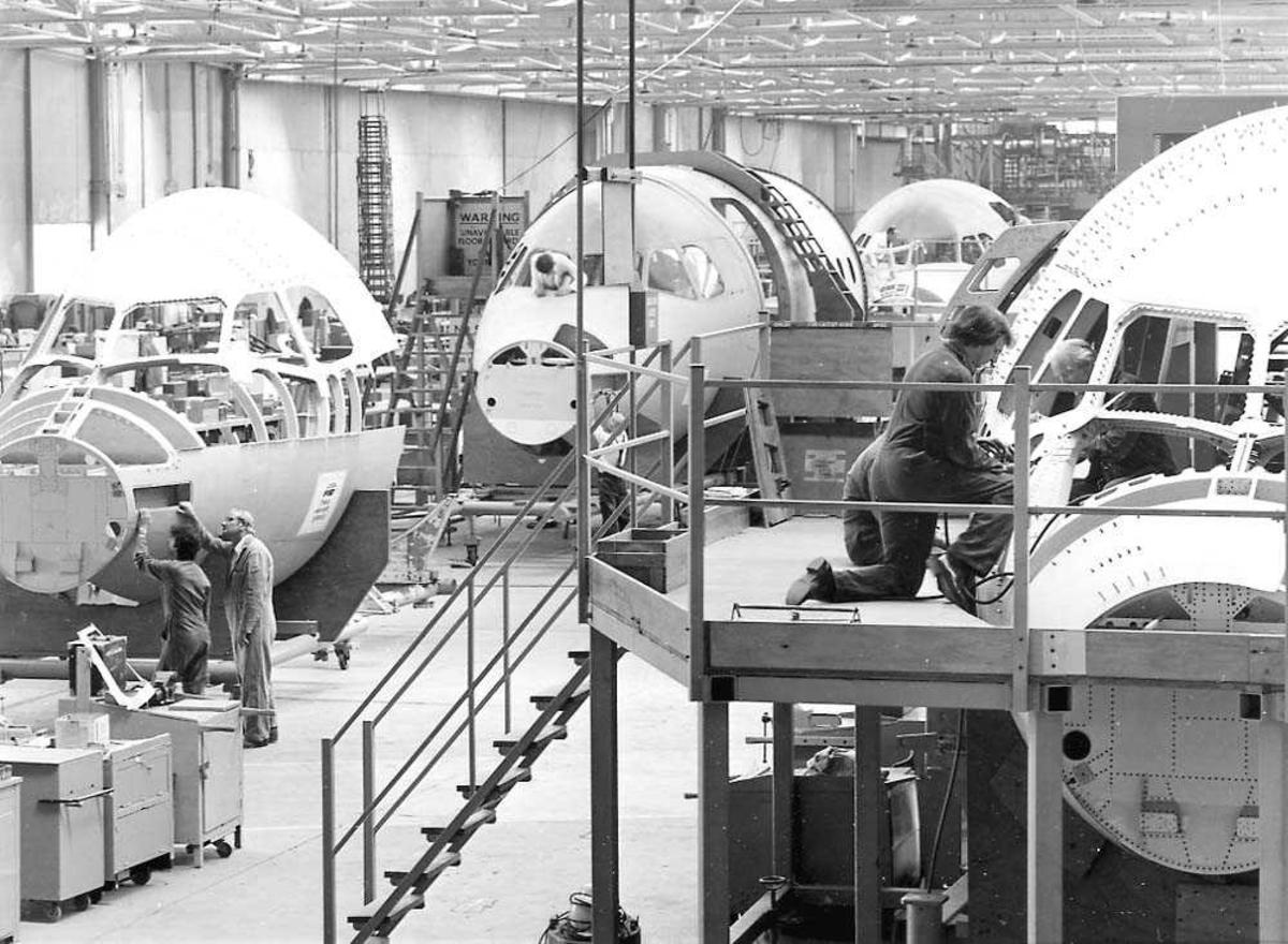 Flere nesepartier av BAe 146 inne i en flyfabrikk, som klargjøres til ferdigmontering. Flere personer som arbeider ved flyene.