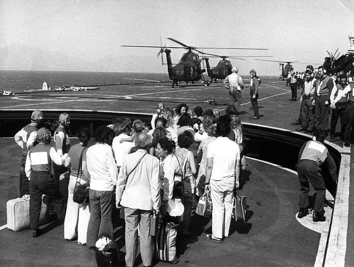 En gruppe personer på et hangarskip, sivile og mannskap. Tre helikoptere i bakgrunnen, Westland Wessex.
