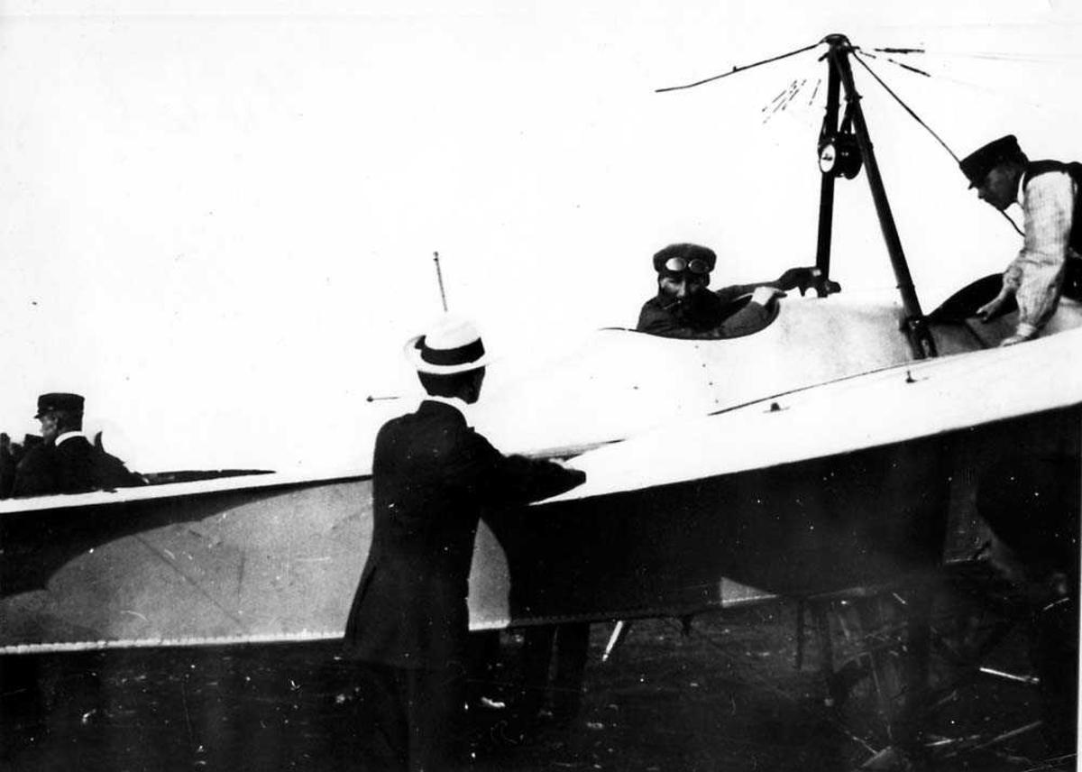 """Ett fly på bakken med en person i cockpiten, Rumpler Taube """"Start"""". To personer ved flyet."""