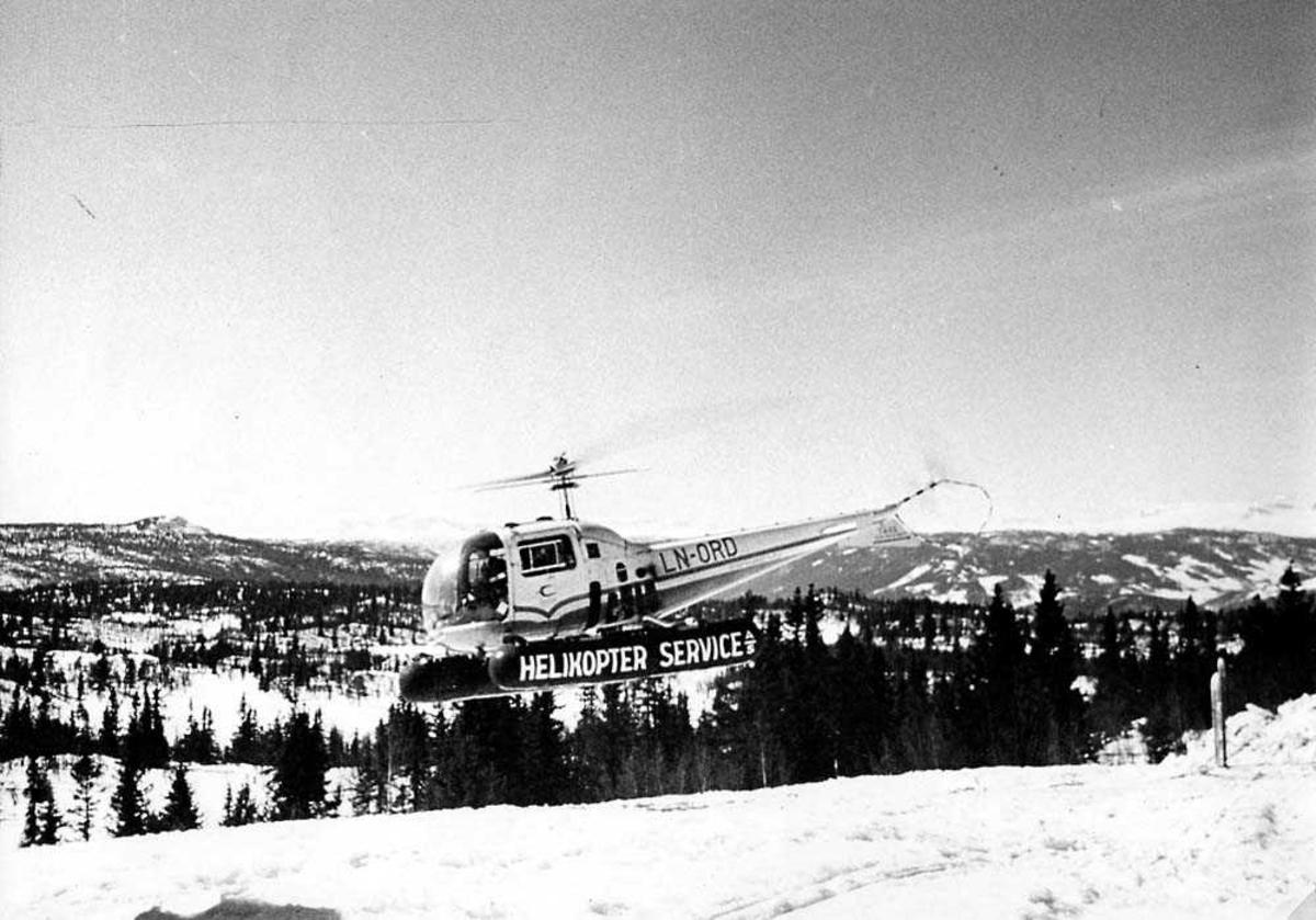 Luftfoto. Ett helikopter i luften, Bell 47 J Ranger LN-ORD fra Helikopter Service A/S. Fjell i bakgrunnen. Snø på bakken.