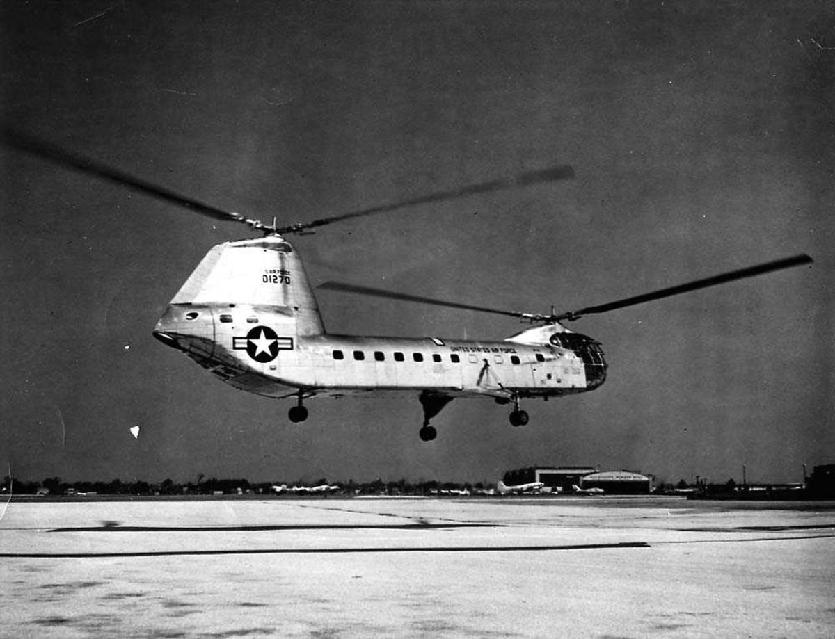 Lufthavn. Ett helikopter i luften like over bakken, Piasecki PV-15 YH-16A. Flere fly på bakken i bakgrunnen.