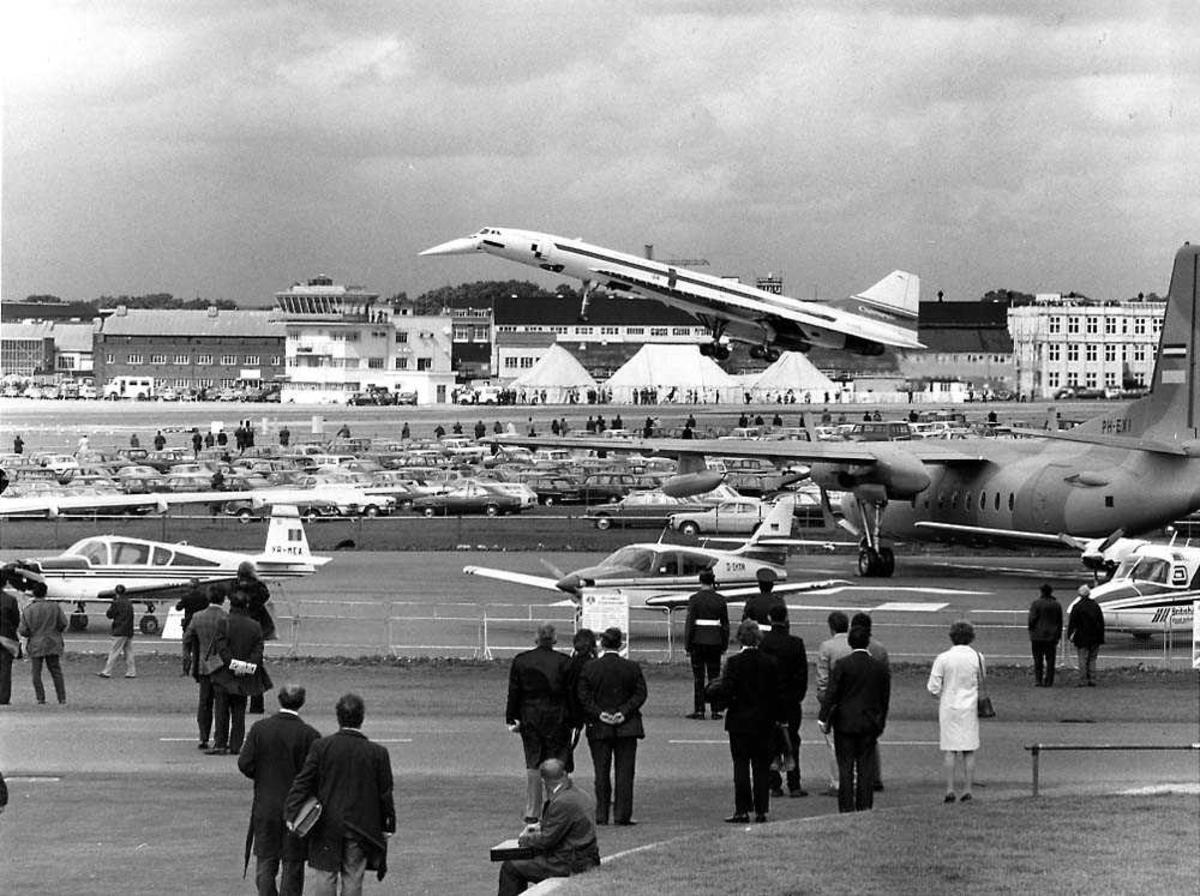 Flystevne. Ett fly i luften like over rullebanen, Concorde 01. Flere andre fly på bakken. Flere personer. Bygninger i bakgrunnen.