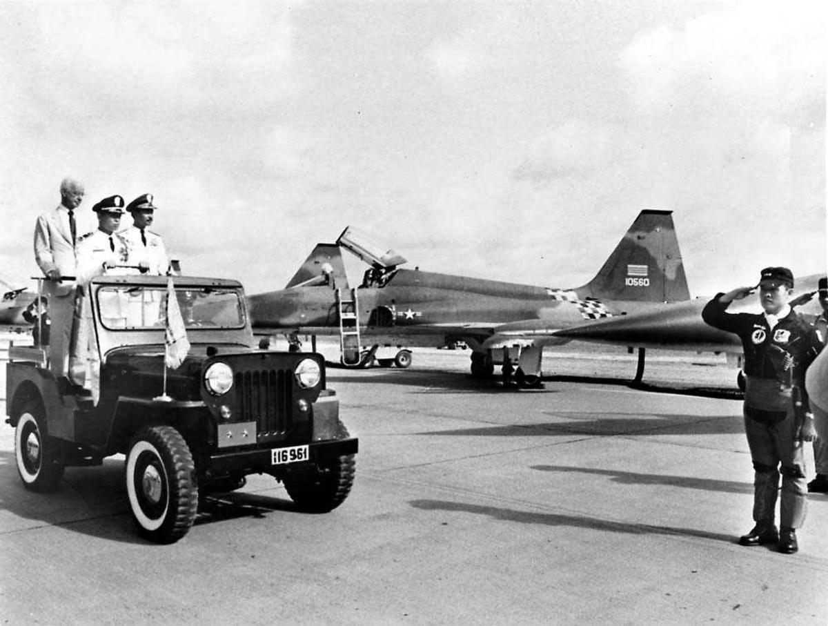 Lufthavn. Ett fly på bakken, Northrop F-5 A/B Freedom Fighter. Flere personer  foran flyet, tre står på en bil.
