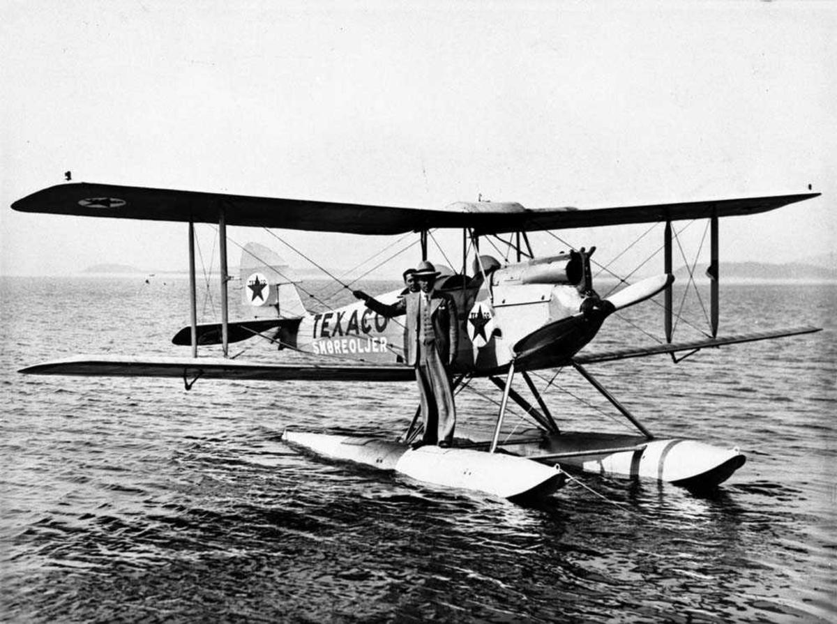 Ett fly ute på vannet, DH-60 Moth M fra Widerøes Flyveselskap. En personer står på den ene flotøren til flyet, en person i cockpiten.
