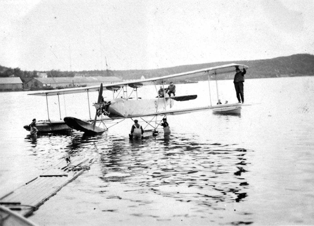 Ett fly på vannet, MF-8. Flere personer på og ved siden av flyet. To båter ved flyet. Bygninger og fjell i bakgrunnen.