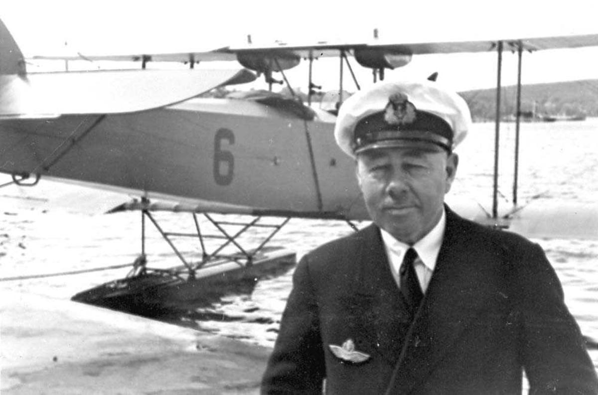 Portrett. En person, mann i uniform. Ett fly på vannet bak personen, MF-8.