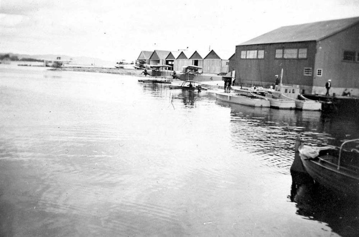 Sjøflyhavn. Flere fly og båter som ligger ved kai. Flere bygninger, bl. a. hangarer.