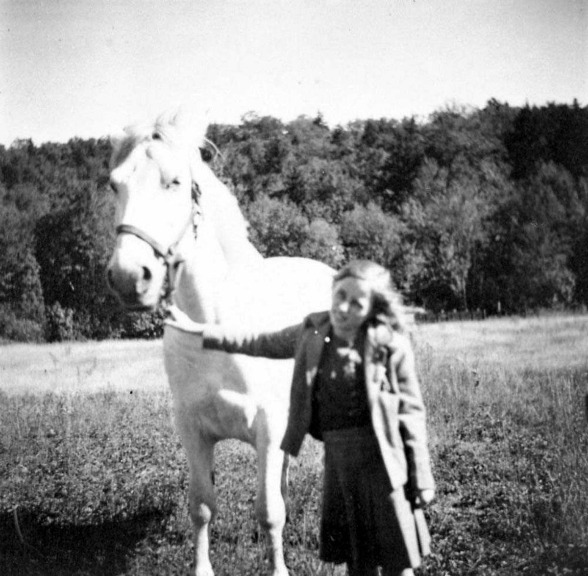 Portrett. En person som står ved en hest, kvinne.