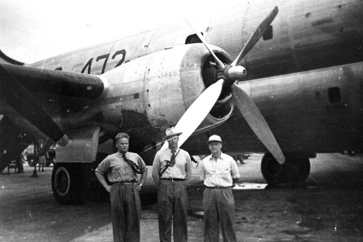 Portrett. Tre personer som står foran en flymotor, menn.