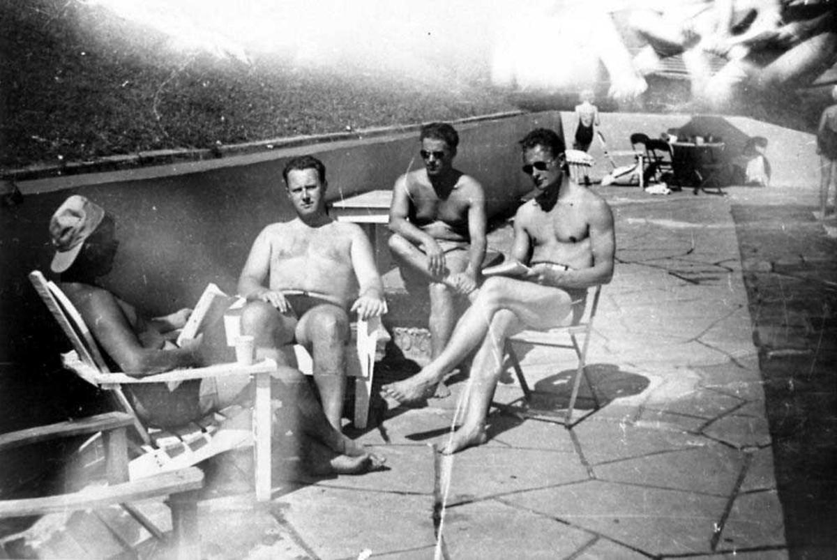 Portrett. Fire personer som sitter ved et svømmebasseng, menn.