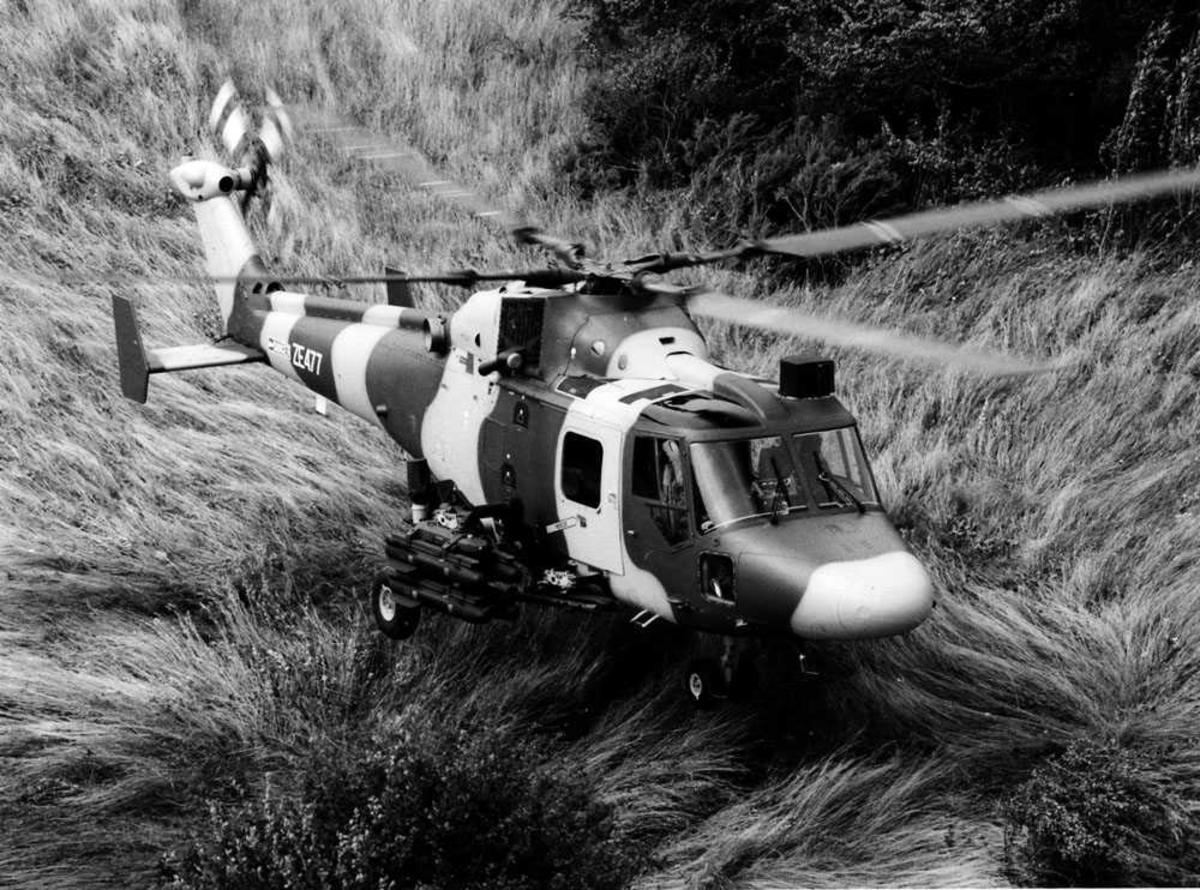 Ett helikopter like over bakken i kamuflasjefarger. Westland Lynx 3 merket ZE477. 4 missiler (Hellfire) hengende på siden.