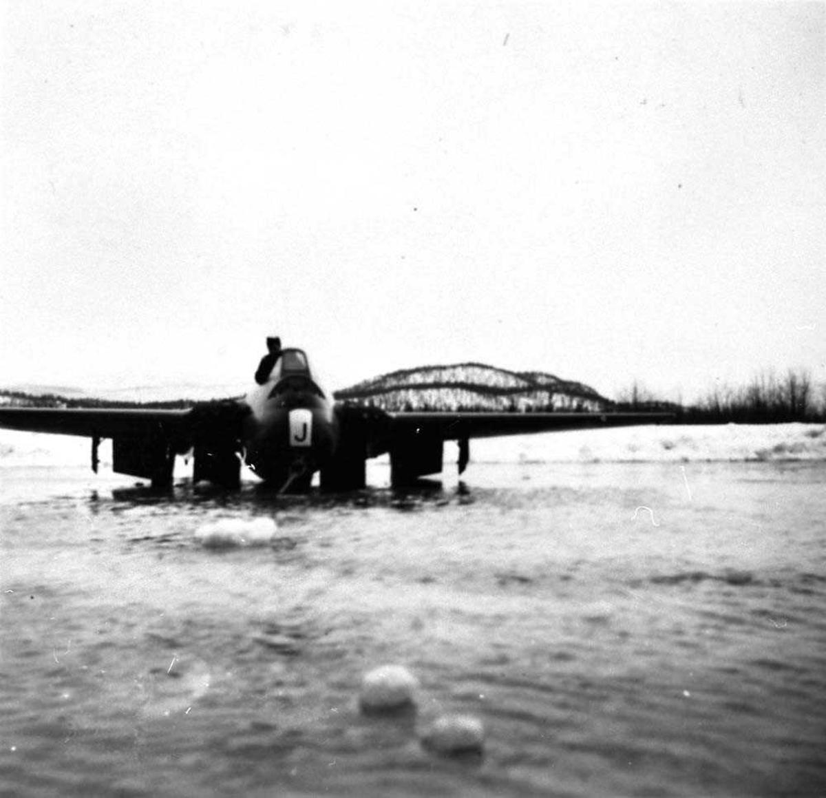 Ett fly som står i et vann, Vampire FB. Mk. 52. En person i flyet.