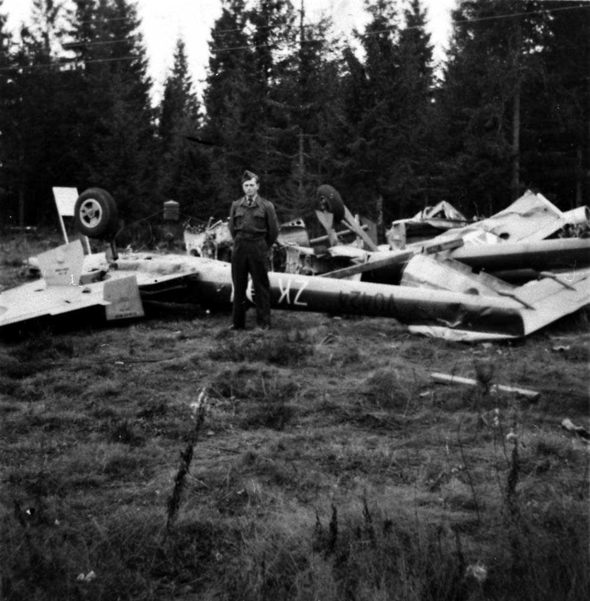 Ett fly som ligger ødelaget ute i en skog etter et totalhavari, Vampire FB Mk 52. En person står foran flyet.