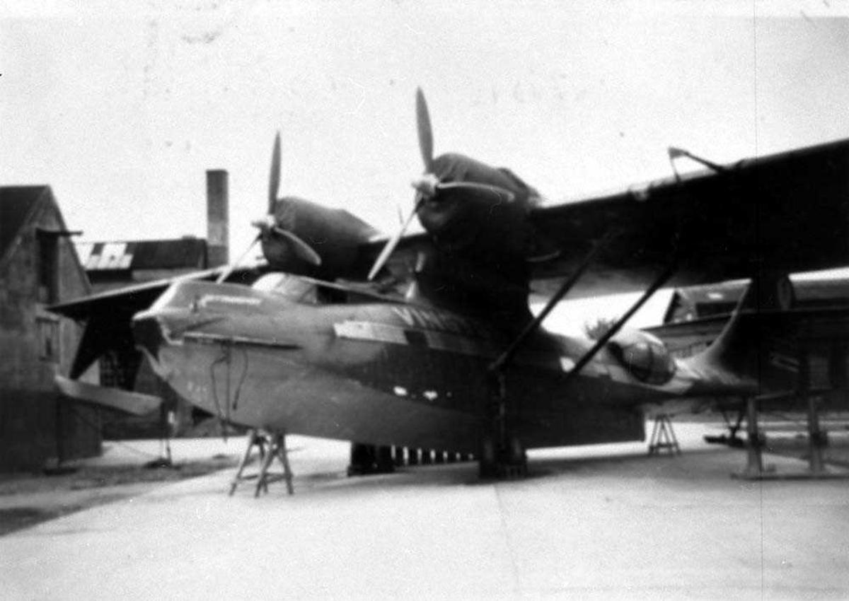 Ett fly på bakken, Catalina PB2B-1 IVB, LN-OAP fra Vingtor Luftveier A/S. Bygninger i bakgrunnen.