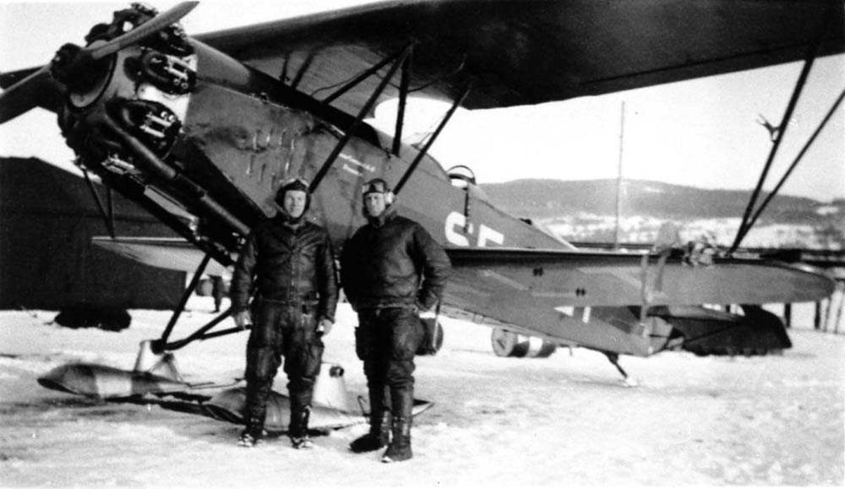 Ett fly på isen SE-ALT. To personer står ved flyet. Snø på bakken.