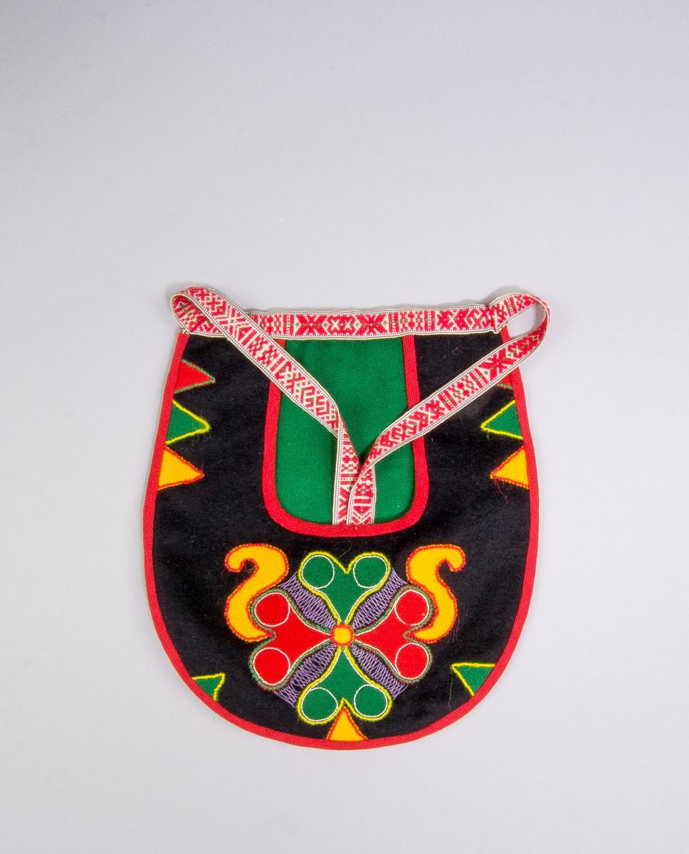 Kjolsäck inspirerad av kjolsäckarna från Leksands socken, Dalarna.. Modell med u-formad öppning. Tillverkad av svart ylletyg, kläde, med applikation av kläde i rött, gult och grönt, fastsydd med läggsöm. Centralt placerad hjärtblomma med slingor och trekanter på sidorna. Broderi utfört med bomullsgarn i flera färger: flätsöm och stjälksöm. Framstycket fodrat med svart bomullstyg, tuskaft. Kantat med rött diagonalvävt ylleband. Bakstycke av svart kläde med grönt kläde monterat i öppningen. Midjeband handvävt, med plockat mönster av rött ullgarn på vit botten.