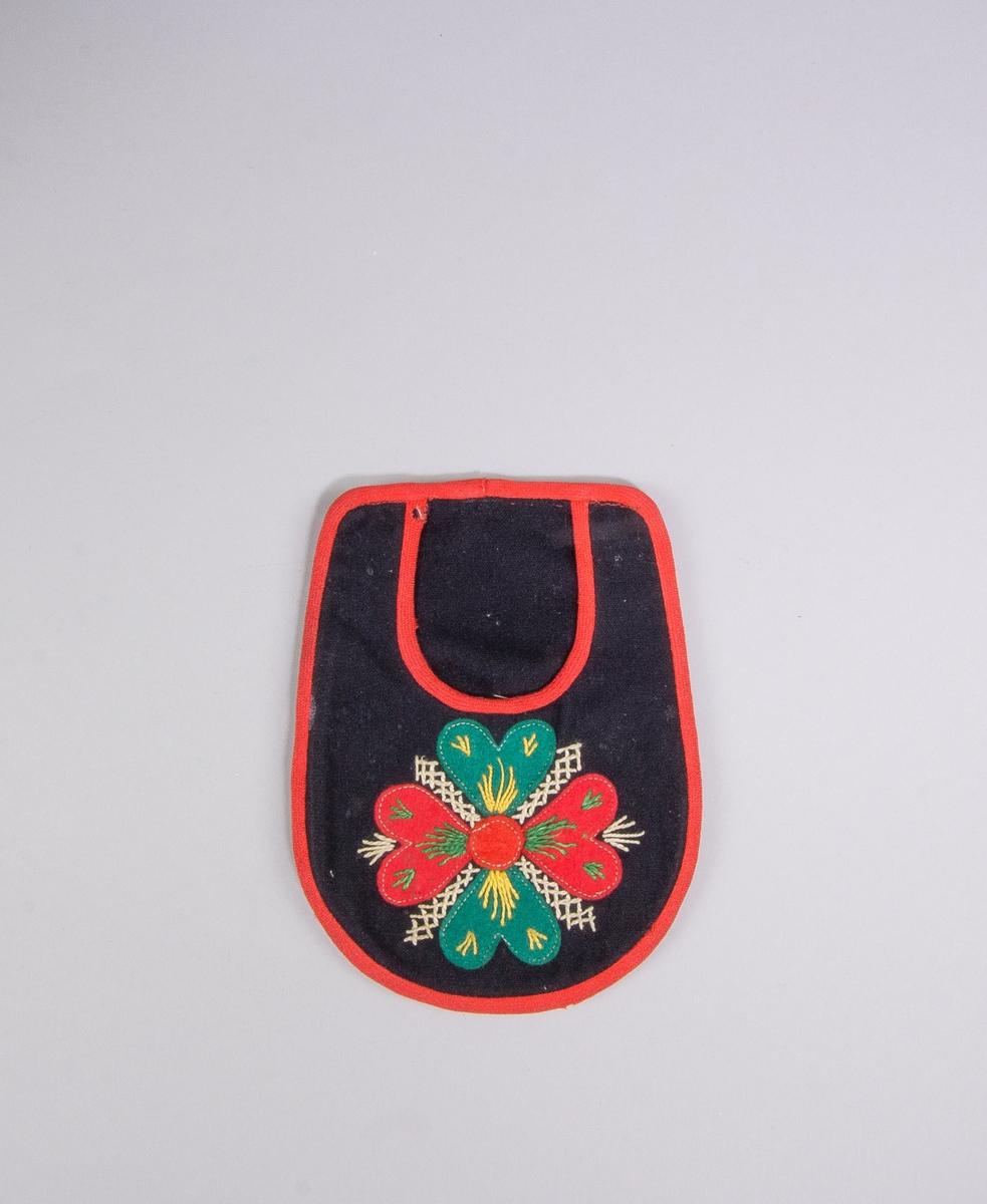 Kjolsäck, inspirerad av kjolsäckarna från Leksands socken, Dalarna. Modell med u-formad öppning. Tillverkad av svart ylletyg, kläde, med applikation av kläde i rött och grönt, fastsydd med maskinsöm. Motiv: hjärtblomma. Broderi utfört med bomullsgarn i vitt, grönt och gult: flätsöm och sticksöm. Framstycket fodrat med rutigt bomullstyg, blått och vitt, tuskaft. Märkt med liten fabriksvävd namnlapp på insidan: L L. Kantat runtom med rött diagonalvävt ylleband. Bakstycke av svart kläde.