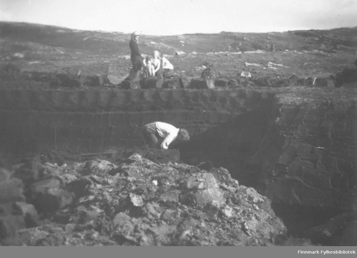 Torvstikking og torvskjæring i Kokelv. Ulrik Larsen står bøyd nederst på bildet. Overfor til venstre står hans datter Julie. Hans kone Ragnhild sitter. Det ses fjell i bakgrunnen