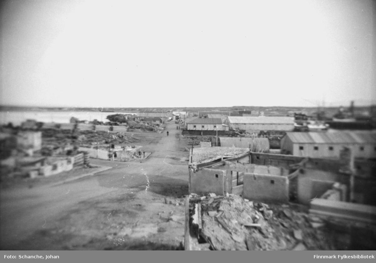 Ruiner i Vadsø -46. Bildet er fra Tollbugata ned mot kai. Bare grunnmurene står igjen av husene på begge sider av gaten.  Gjenreisningen har begynt og det står et par nybygg og brakker her og der.