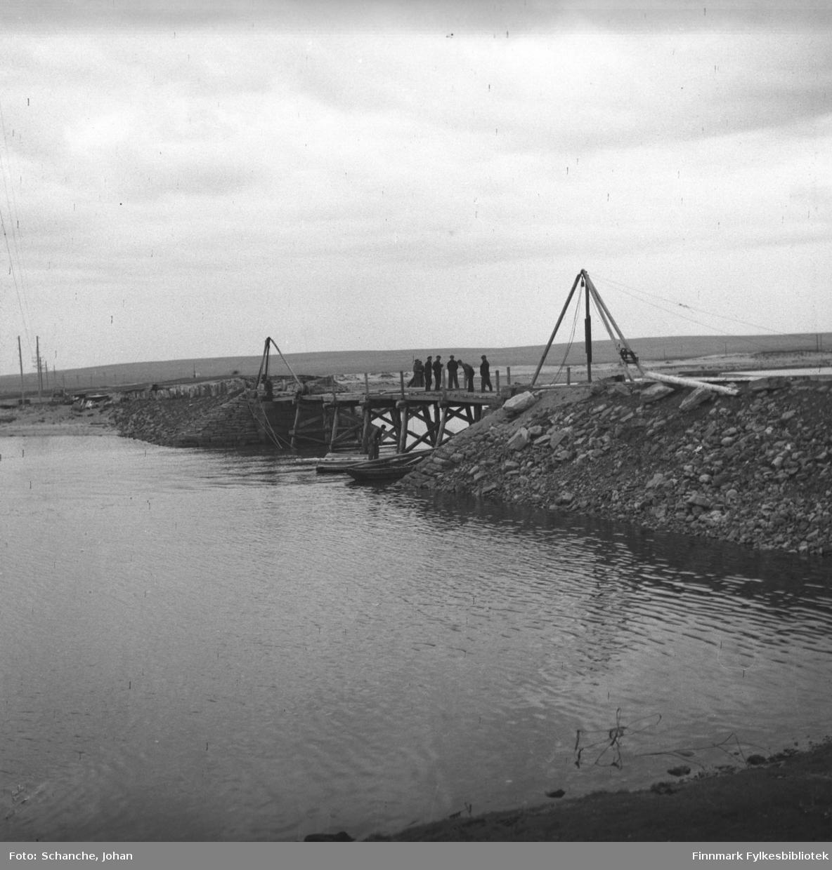 Den ødelagte brua i Skallev repareres. Arbeidere står på brua og jobber.  Et par båter ligger under brua. På det ene står en mann.  Bildet er tatt fra elvebredden fra lang avstand.