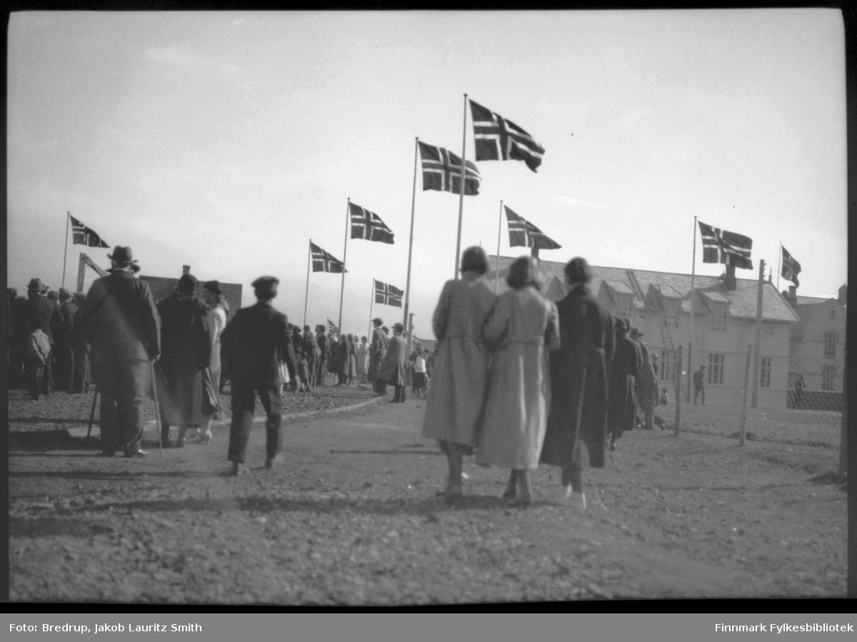 Byjubileet 1933 - Vadsøs 100-årsjubileum. Mange tilskuere på vei opp mot festplassen - veien går forbi folkeskolen.  Kvinnene er kledd i kåper og hatter og menn i dress.  Det flagges overalt.  Personene på bildet har ryggen mot fotografen.  Vi ser skolen til høyre i bildet.