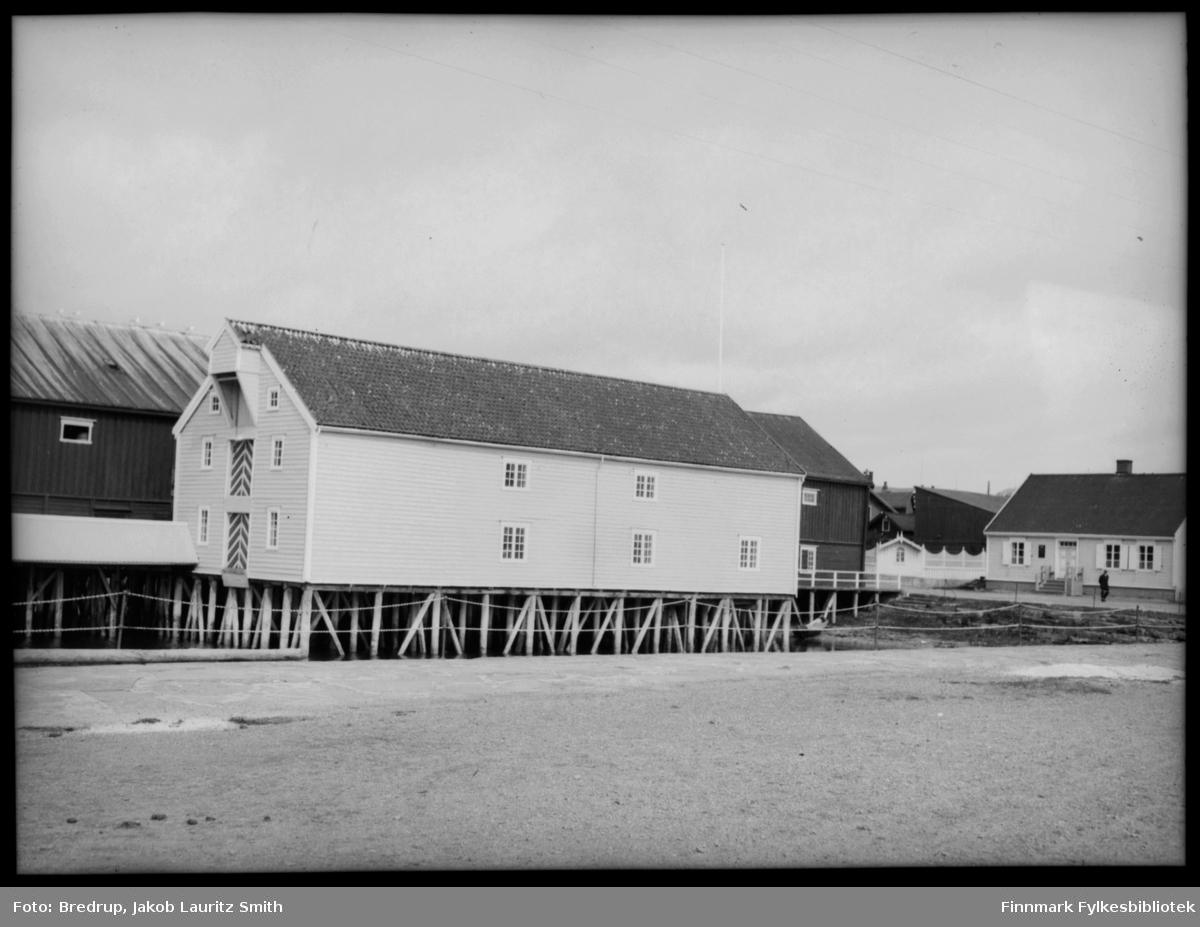 Bildet er tatt nederst i Tollbugata i Vadsø.  Man ser kaier og pakkhus, og Tollboden fotografert rett forfra.  En mann går i gata.