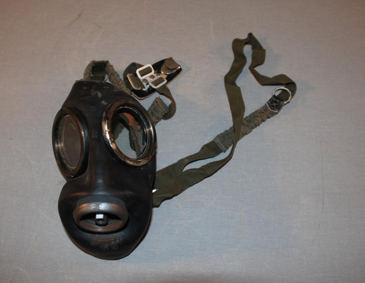 Gassmaske med gass- og støvfilter, bruksanvisning og beholder med lokk til oppbevaring. Masken er en ansiktsmaske med synsfelt som sirkelrunde glassflater. Fem festereimer ender i et samlepunkt på en lærplate. Rundt festepunkt for filtertilsats. Påinnsiden er masken foret med tekstil rundt kanten. Reim for oppheng av masken.