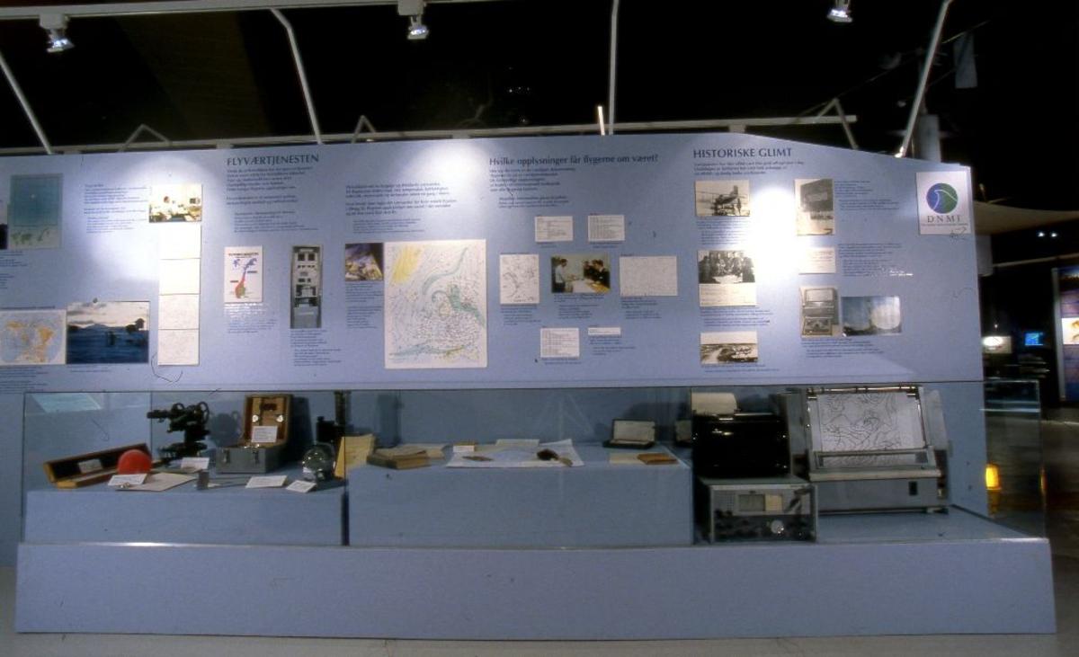 Vegg med bilder, tekst og gjenstander. Flyværtjenesten. Diverse hjelpemidler ifm værobservasjoner.