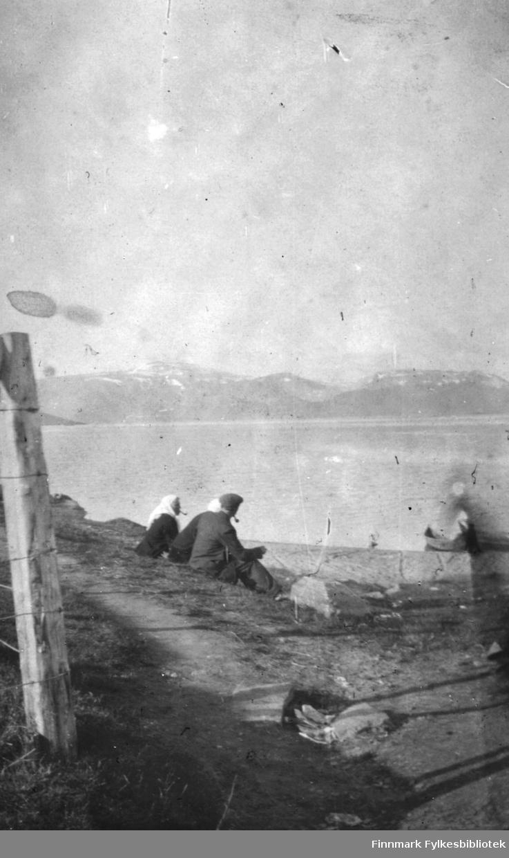 Mann og to kvinner med hvite skaut sitter ute på Langnes i Tana. Mannen og i hvert fall en av kvinnene røyker pipe