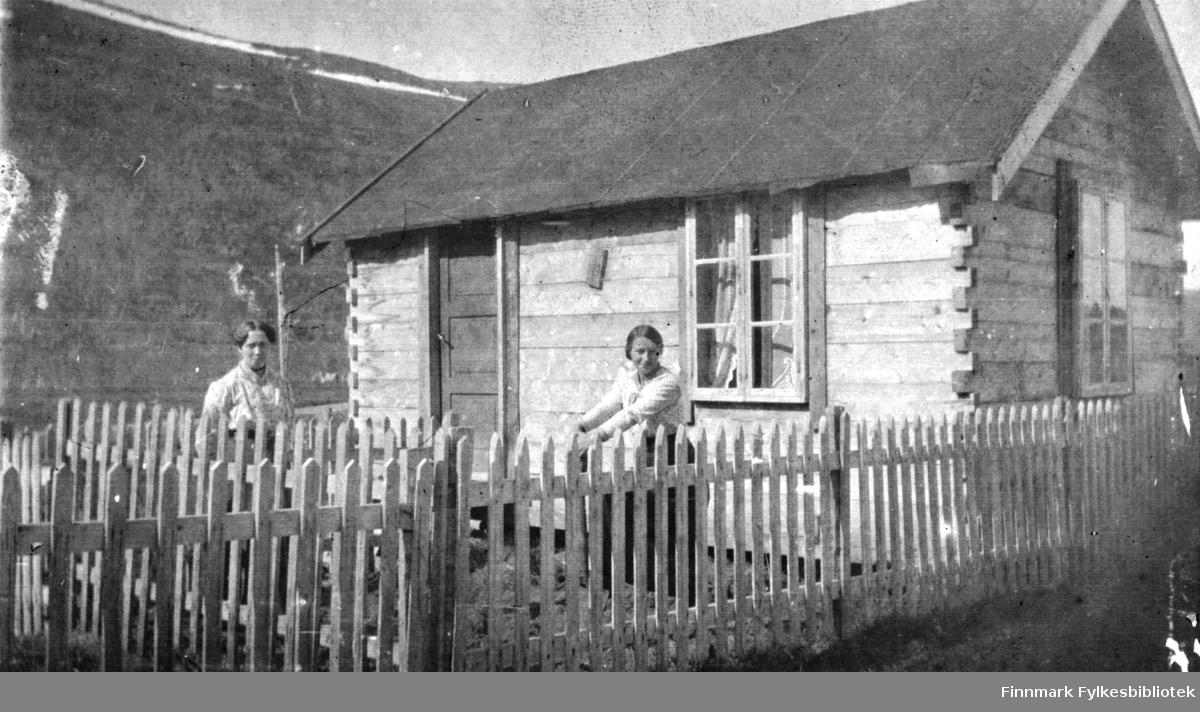To kvinner utenfor et lite, laftet tømmerhus på langnes i Tana
