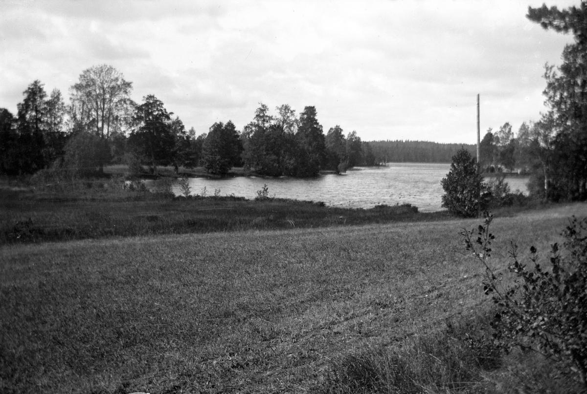 Ett landskap med en sjö, skog och fält.
