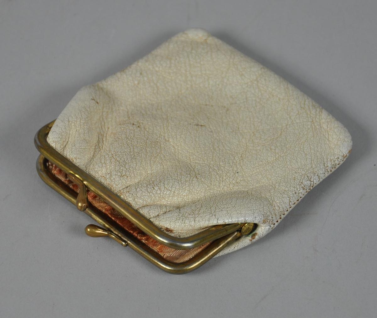 Hvit skinnpung med trykklås og beslag av metall. Pungen har silkefôr.