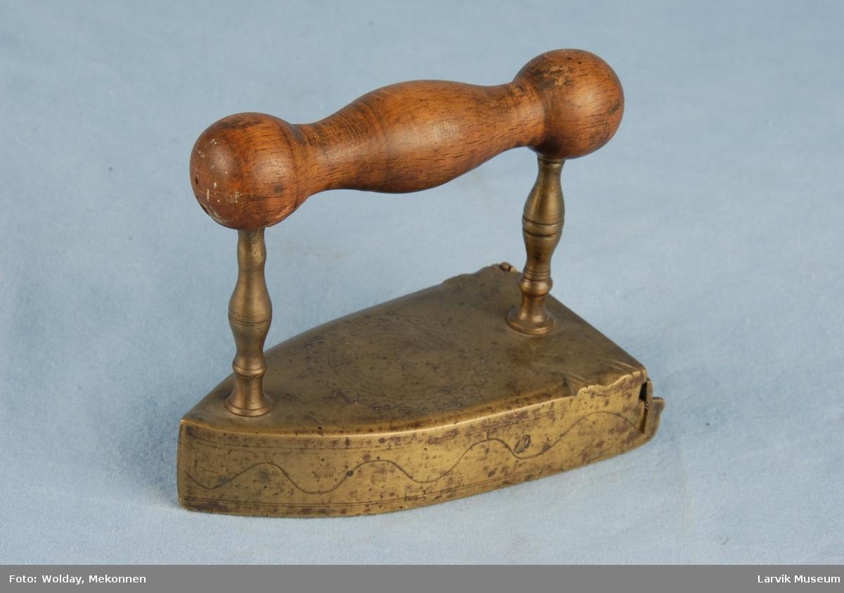 Form: Trekantet hul  med rissede ornamenter. Håndtak i tre, Trekantet bolt inni. Med bolt som varmes opp.