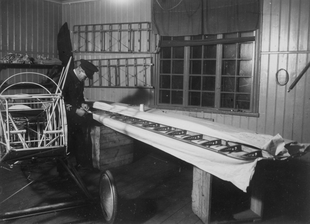 Flygplansbygge. Tyghantverkare George Holmberg i arbete med att klä en flygplansvinge med duk på flygplanet Holmberg Racer.