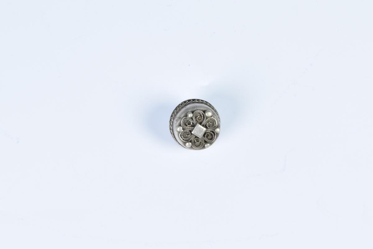 Knapp av sølv med filigransarbeid.