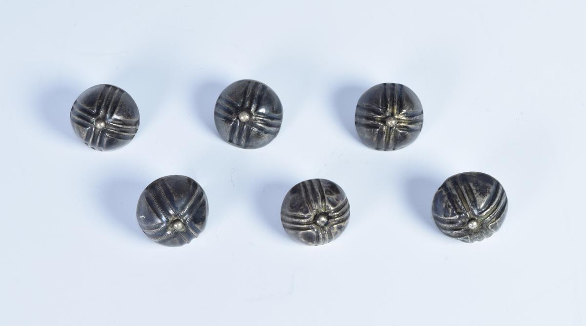 Seks sølvknapper dekorert med fire felt med parallelle forsenkede linjer som danner et likearmet kors.