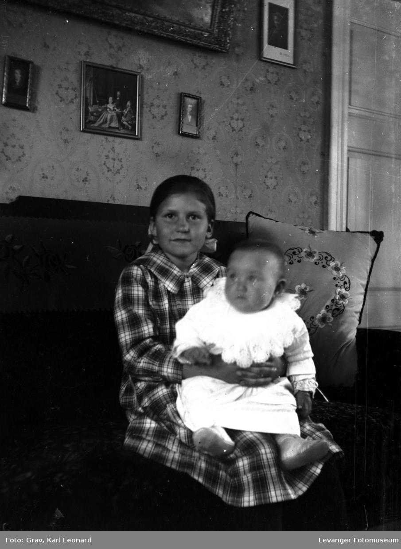 Portrett, jente med barn på fanget