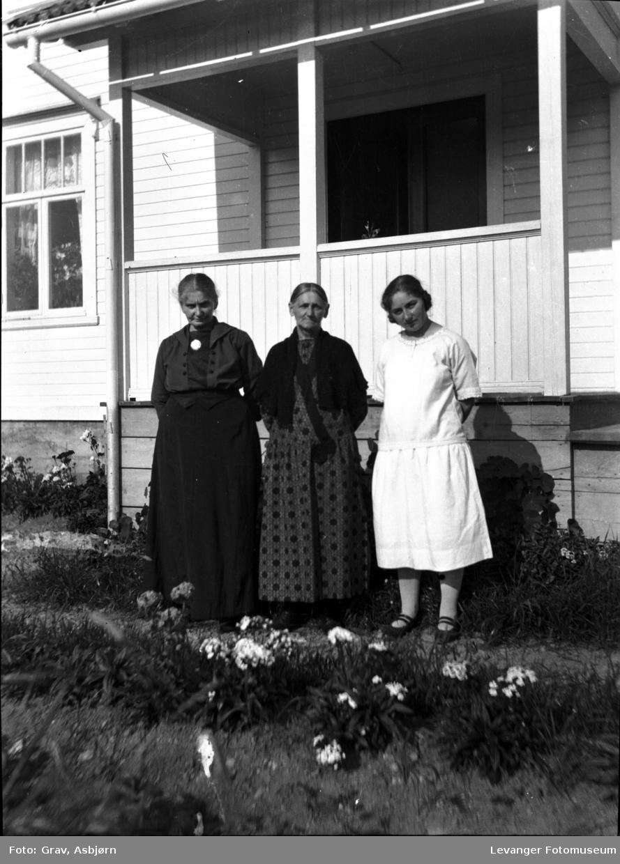 Gruppebilde, tre kvinner ved veranda.